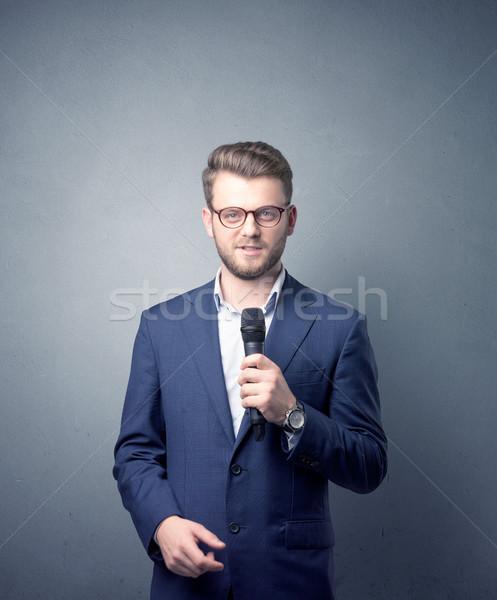 üzletember tart mikrofon beszél kék háttér Stock fotó © ra2studio