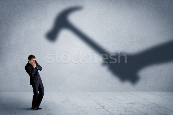 Business person afraid of a shadow hand holding hammer concept Stock photo © ra2studio