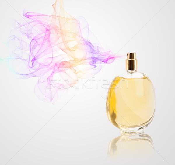 Stock photo: Perfume bottle spraying colored scent