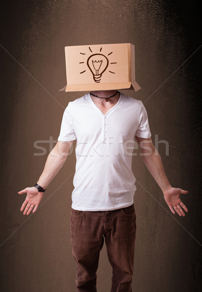 Young man gesturing with a cardboard box on his head with light  Stock photo © ra2studio