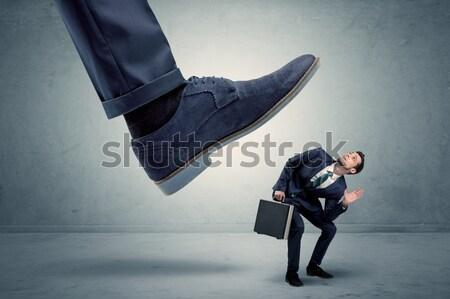 Employee getting trampled by big shoe Stock photo © ra2studio
