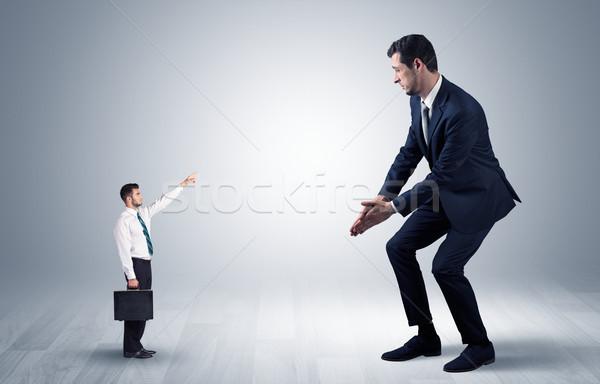 Small businessman pointing to a giant businessman Stock photo © ra2studio