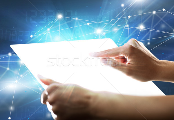 Hands touching a glass-like tablet  Stock photo © ra2studio