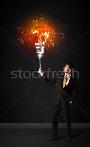Businessman with an explosion bulb Stock photo © ra2studio