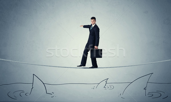 Businessman walking on rope above sharks Stock photo © ra2studio