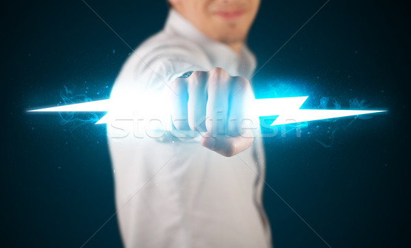 Stock photo: Business man holding glowing lightning bolt in his hands
