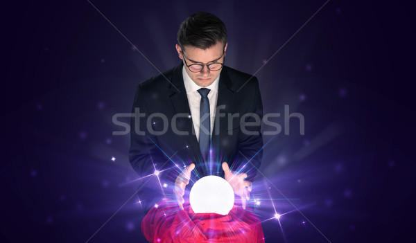Businessman sitting with crystal ball in action Stock photo © ra2studio
