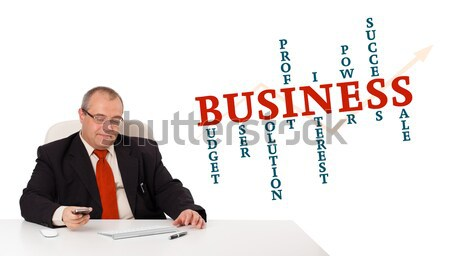 businessman sitting at desk and holding a mobilephone with business word cloud, isolated on white Stock photo © ra2studio