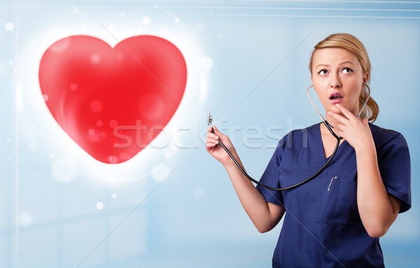 Fiatal nővér gyógyító piros szív csinos Stock fotó © ra2studio