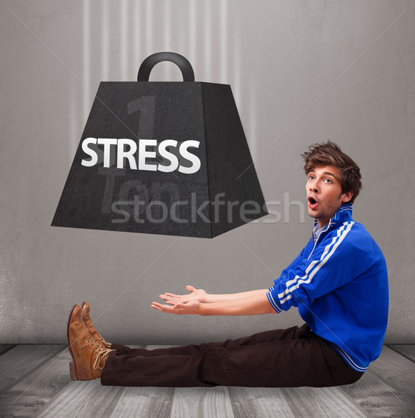 Handsome boy holding one ton of stress weight Stock photo © ra2studio