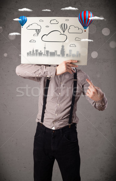 Businessman holding a cardboard with cityscape in front of his h Stock photo © ra2studio