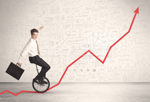 Stock photo: Business parson riding unicycle on an uprising red arrow