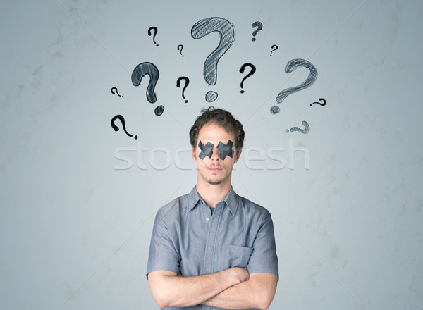 Young man with glued eye and question mark symbols Stock photo © ra2studio