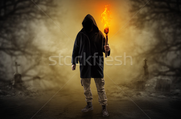 Stock photo: Man coming out from a thicket with burning flambeau