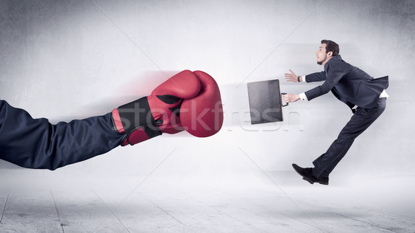 Stock photo: Huge Boxing Gloves punches businessman concept
