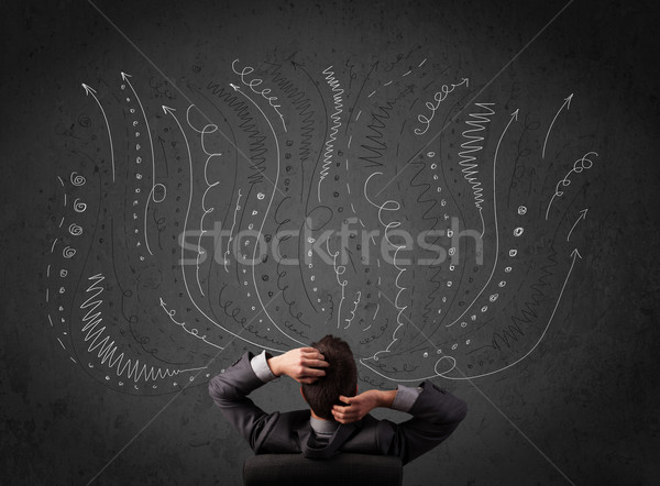 Thoughtful young businessman sitting and deciding in front of a chalkboard with sketched arrows Stock photo © ra2studio