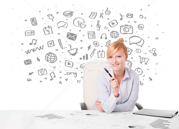 Beautiful young businesswoman with all kind of hand-drawn media icons in background Stock photo © ra2studio