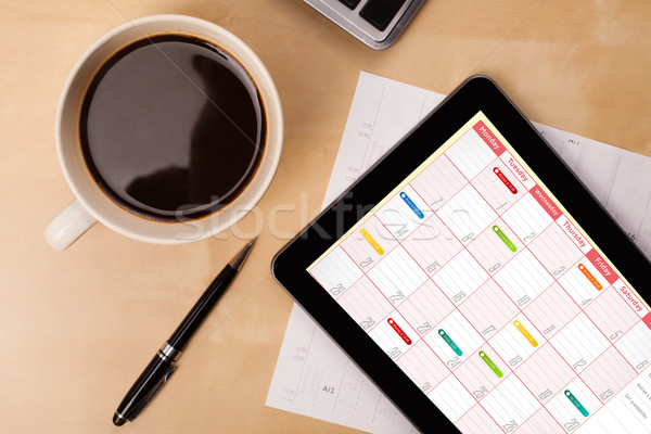 Workplace with tablet pc showing calendar and a cup of coffee on a wooden work table closeup Stock photo © ra2studio