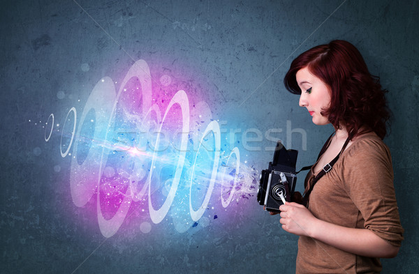 Photographer girl making photos with powerful light beam Stock photo © ra2studio