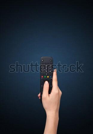 Hand with remote control Stock photo © ra2studio