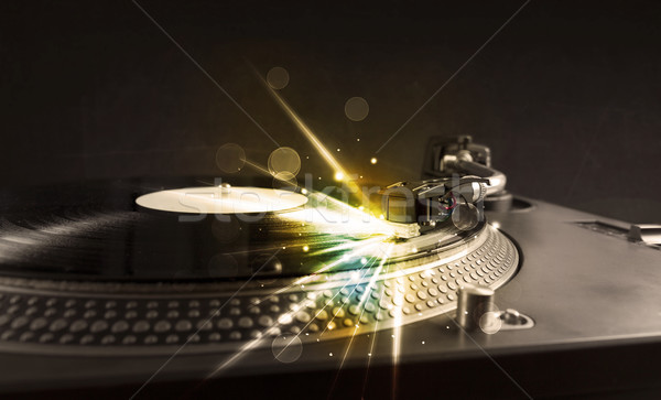 Music player playing vinyl with glow lines comming from the need Stock photo © ra2studio