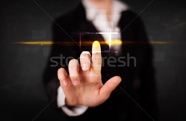 Young tech lady touching button with orange light beams concept Stock photo © ra2studio