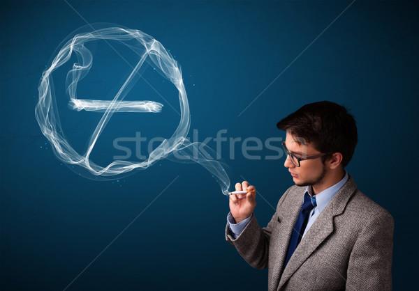 Jeune homme fumer malsain cigarette signe Photo stock © ra2studio