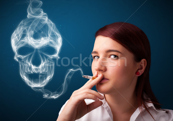 Young woman smoking dangerous cigarette with toxic skull smoke  Stock photo © ra2studio
