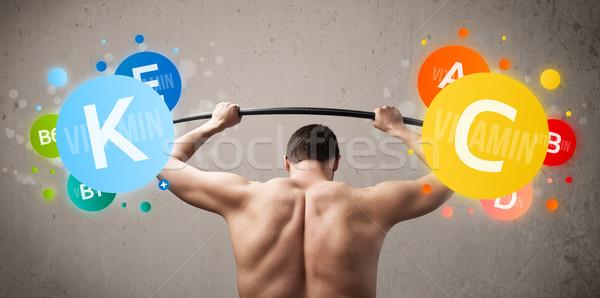 skinny guy lifting colorful vitamin weights Stock photo © ra2studio