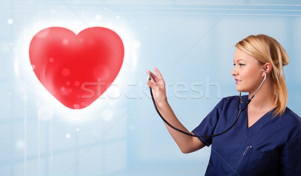 Młodych pielęgniarki uzdrowienie czerwony serca dość Zdjęcia stock © ra2studio