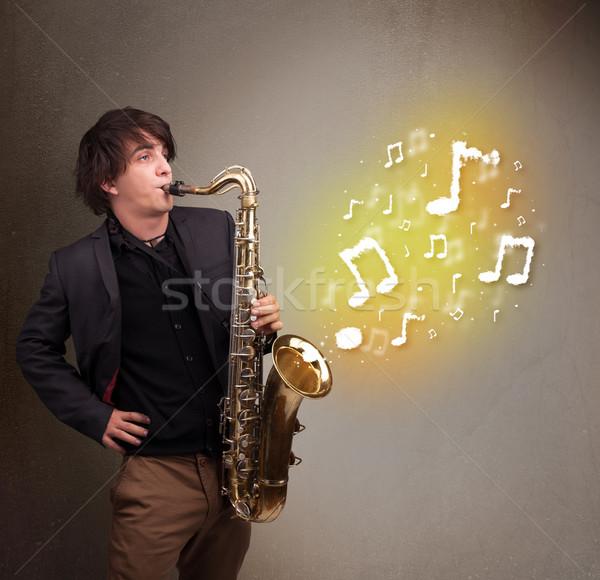 Guapo músico jugando saxófono notas musicales jóvenes Foto stock © ra2studio