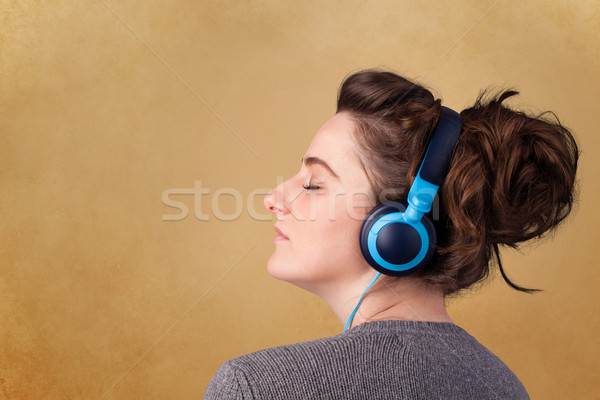 Young woman with headphones listening to music with copy space Stock photo © ra2studio