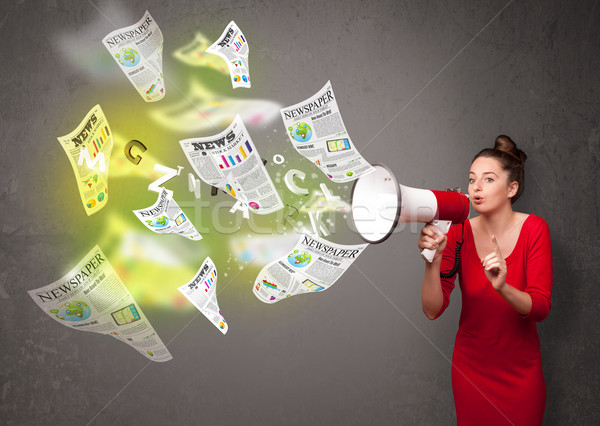Girl yelling into loudspeaker and newspapers fly out Stock photo © ra2studio