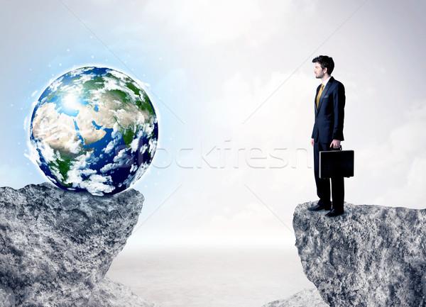 Businessman on rock mountain with a globe Stock photo © ra2studio