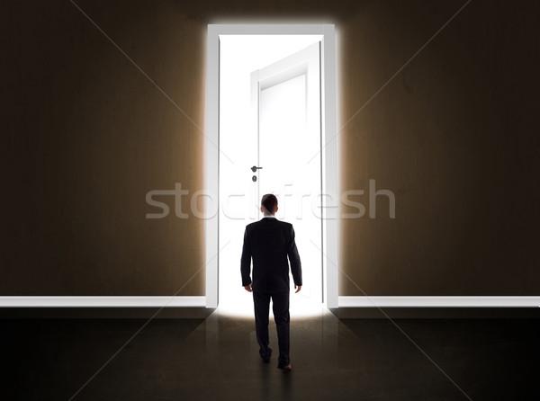 Business man looking at big bright opened door Stock photo © ra2studio