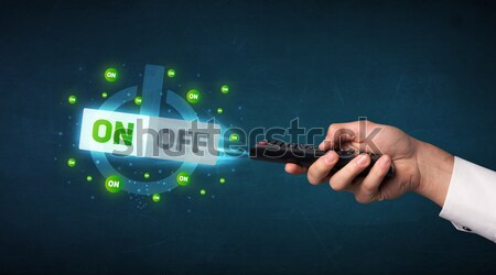 Hand with remote control and on-off signals Stock photo © ra2studio