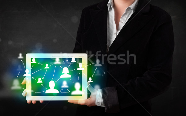 Young person presenting tablet with green social media icons Stock photo © ra2studio