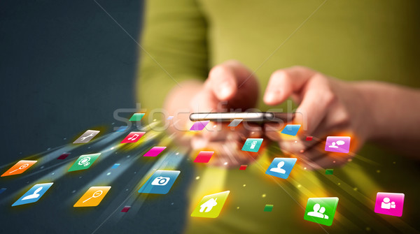 Man holding smartphone with technology application icons Stock photo © ra2studio