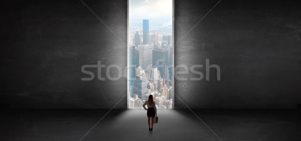 Woman looking to a cityscape from a dark empty room Stock photo © ra2studio
