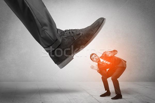 Large foot stepping down small man Stock photo © ra2studio