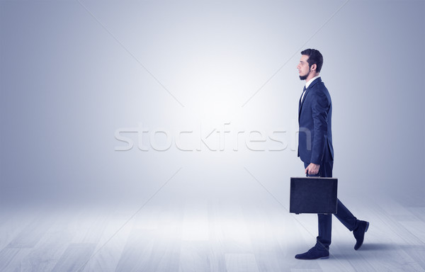 Businessman walking in front of an empty wall Stock photo © ra2studio