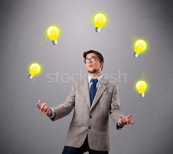 Stock photo: young man standing and juggling with light bulbs