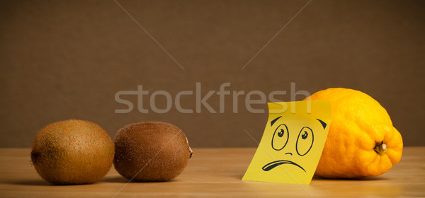 Lemon with sticky post-it note looking sadly at kiwis Stock photo © ra2studio