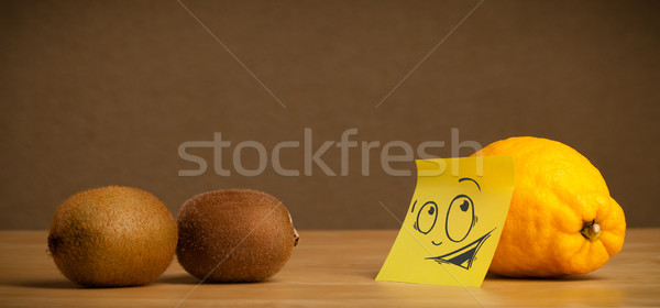 Lemon with post-it note looking curiously at kiwis Stock photo © ra2studio