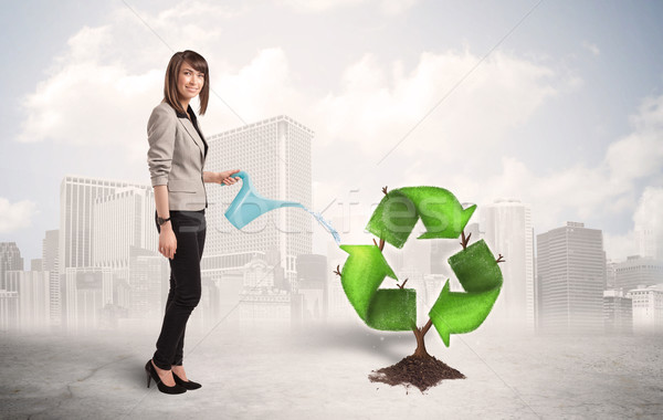 Business woman watering green recycle sign tree on city backgrou Stock photo © ra2studio