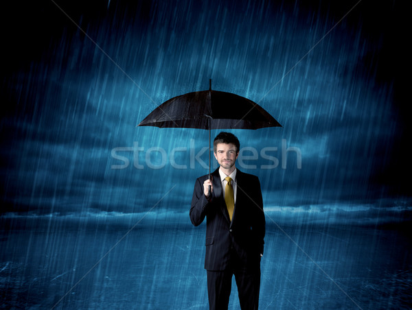 Stock photo: Business man standing in rain with an umbrella