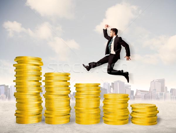 Bem sucedido homem de negócios saltando para cima moeda de ouro dinheiro Foto stock © ra2studio