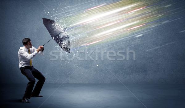 Business man defending light beams with umbrella concept Stock photo © ra2studio