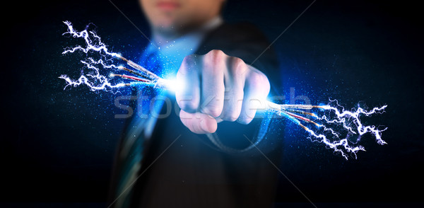 Business person holding electrical powered wires Stock photo © ra2studio