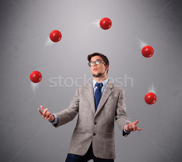 Stock photo: young man standing and juggling with red balls
